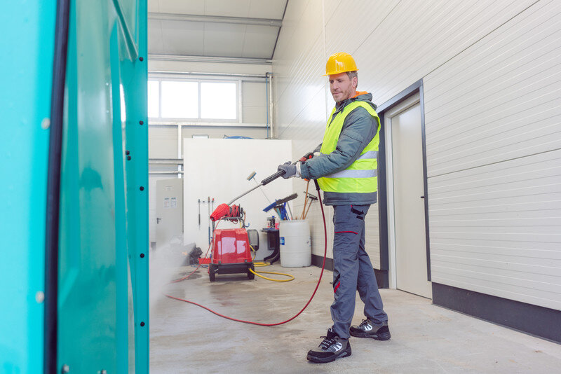 Man Cleaning Portable Toilets